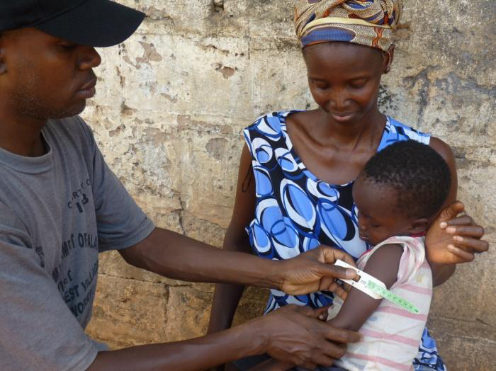 Bubacarr measures the arm of four-year old Musa to check his health